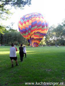 Passagiers helpen mee om de luchtballon op te bouwen in Rotterdam. De ballonvaart, die over het metropool en de stad Rotterdam gemaakt gaat worden start op Rotterdam-Zuid, vlakbij Ahoy.