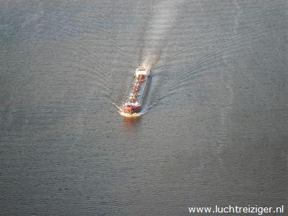 Vlak voor de van Brienenoordbrug zien we een binnenvaartschip. We varen met onze luchtballon van Rotterdm naar de Vlist.