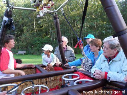 Passagiers kijken in de ballonmand voor een 'laatste inspectie'. Straks maken ze een ballonvaart van Rotterdam-zuid, over de stad, naar Haastrecht.